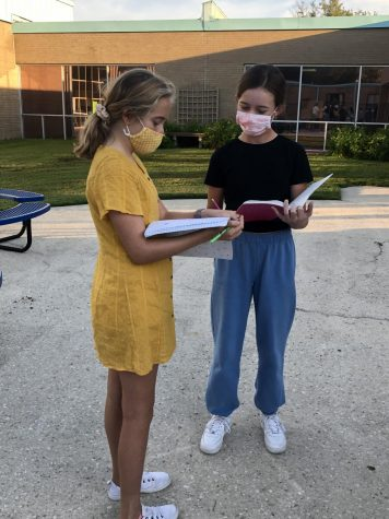 Sadie Bryant and Lauren Barned conducting research while wearing cloth masks.